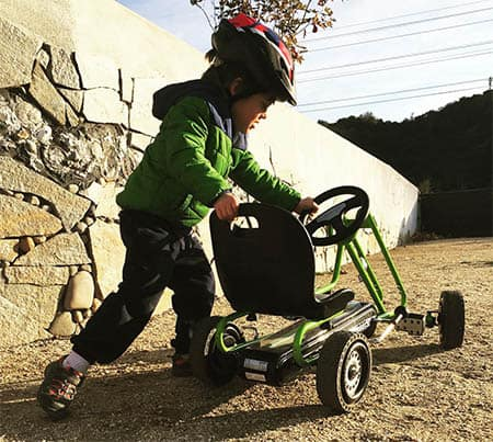 boy playing on pedal power go kart