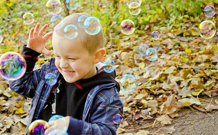 Boy plays with bubble machine