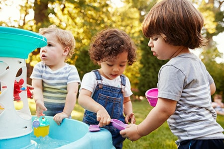 Toddlers playing with water table